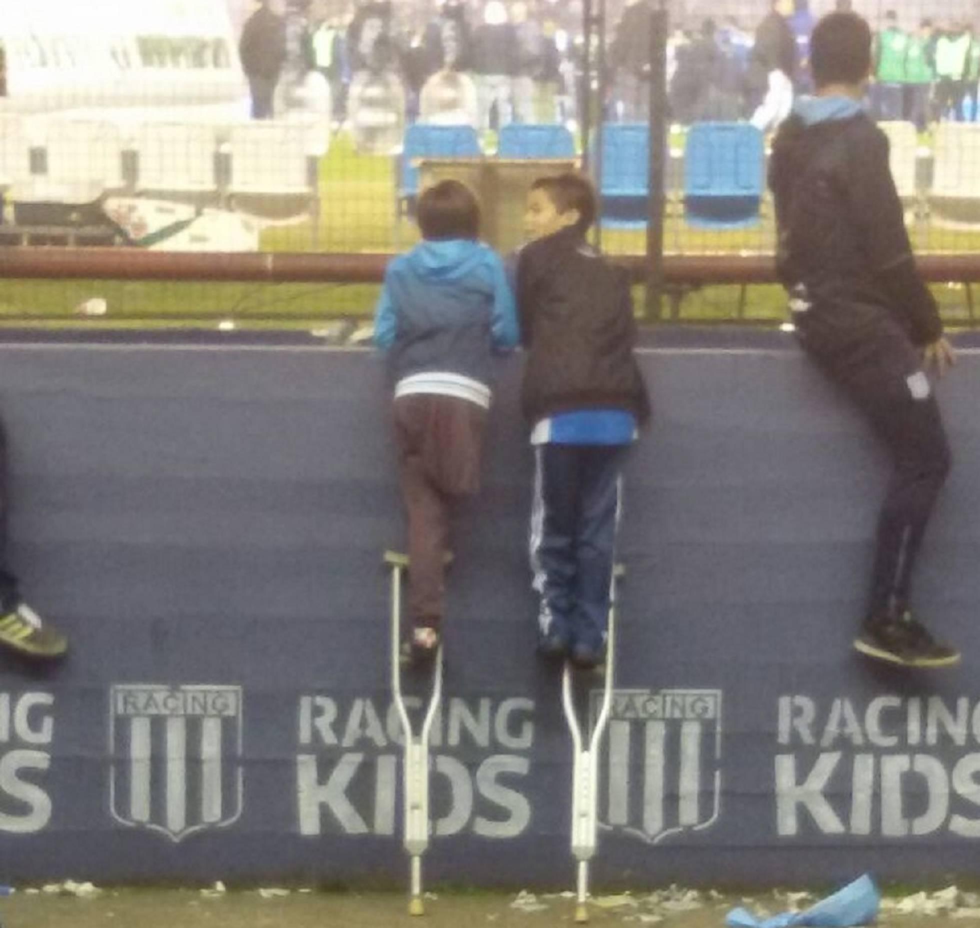 Un niño con pierna amputada presta su muleta a otro para ver un partido