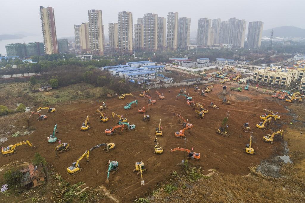 Se pueden ver decenas de excavadoras y otros vehículos de obra trabajando en una explanada. Foto: AFP