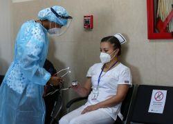 Una enfermera revisa el estado de su colega Cristina Chango, luego de ser vacunada contra la covid-19 en el Hospital Centinela Pablo Arturo Suárez. Foto: EFE