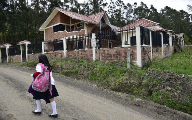 Una menor pasa frente a una casa deshabitada en Déleg, provincia de Cañar. Foto: AFP/Rodrigo Buendía