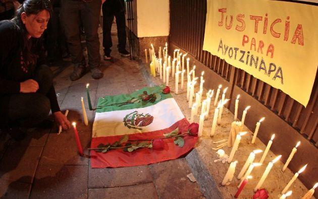 Los manifestantes colocaron velas encendidas, rosas rojas y fotografías de los jóvenes desaparecidos. Foto: AFP