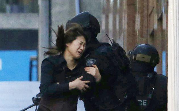 Una rehén corre hacia un policía afuera del Lindt cafe, el 15 de diciembre del 2014.  Foto: Reuters.