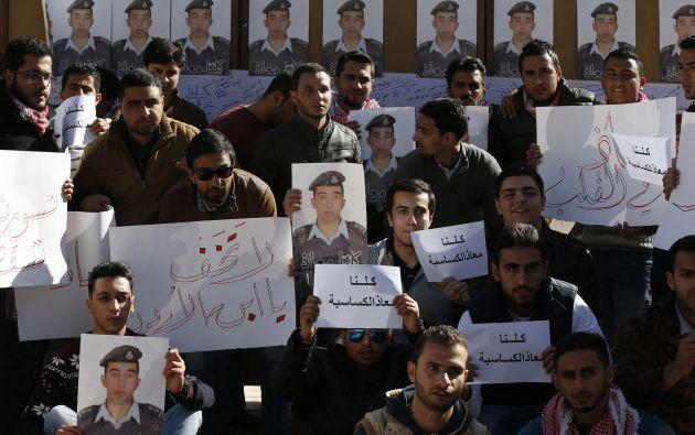 """Un grupo de estudiantes carga fotografías del piloto jordano y carteles que dicen: """"Todos somos Muath"""". Foto: REUTERS"""