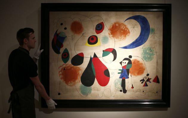 Un empleado en Christie's acomoda el cuadro de Miró. Foto: REUTERS.