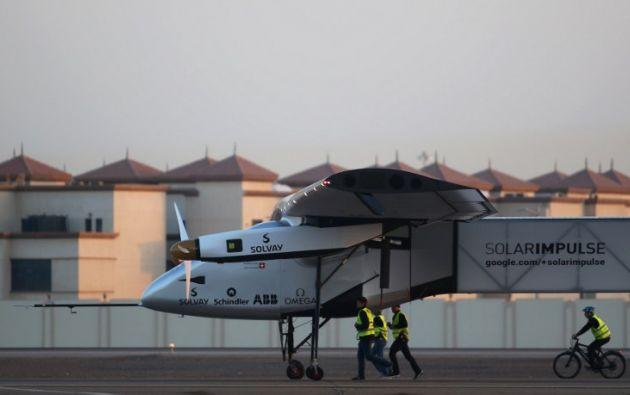 Miembros del equipo del Solar Impulse 2 escoltan al avión en el pequeño aeropuerto de Al-Bateen. Foto: AFP
