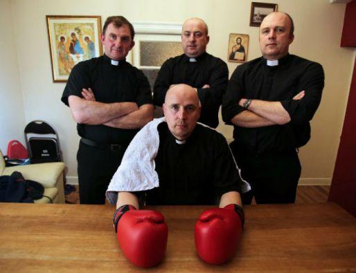 El sacerdote Pierre 'Jalapeño' Pepper posa con su equipo en su casa de la iglesia St. Rynaghs antes de la pelea. Foto: AFP