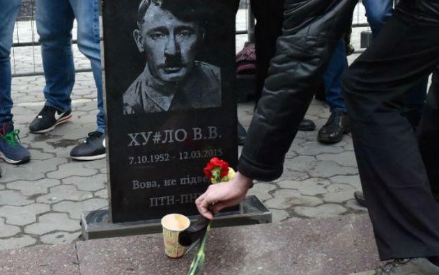 En la lápida Putin aparece representado como Hitler, con las iniciales de su nombre y la fecha de su imaginaria muerte. Foto: AFP