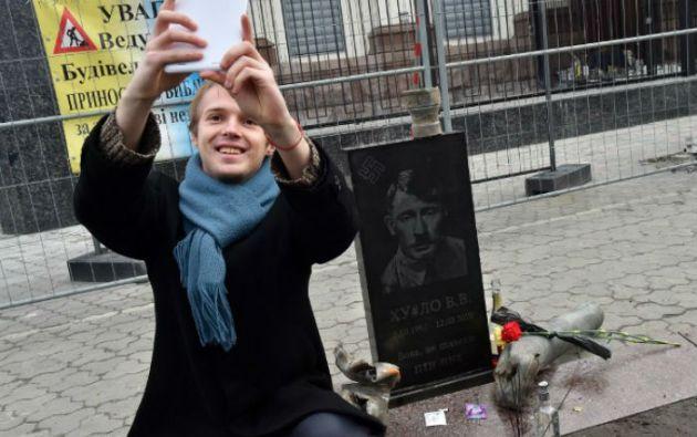 La lápida colocada ante la embajada de Rusia en Kiev atrajo a varios curiosos. Foto: AFP