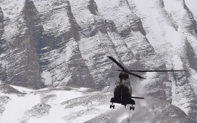 Un helicóptero sobrevuela la zona del accidente, como parte de la investigación. Foto: AFP.