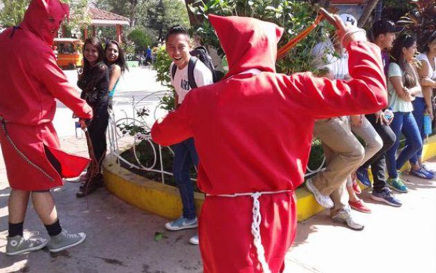 El grupo de hombres vestidos de rojo intenso, encapuchados y armados con látigos recorren las calles del pueblos azotando a los pobladores. Fotos: Twitter.