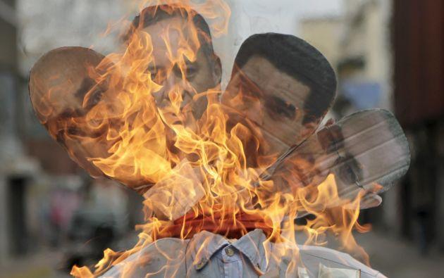 """Un monigote de cuatro cabezas,que representan a Maduro y otros miembros del gabinete, es prendido durante la """"Quema del Judas"""" en Caracas. Foto: REUTERS"""