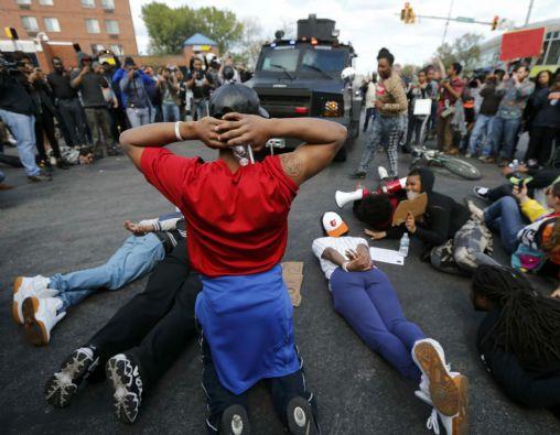 Un grupo de jóvenes protestan frente a un vehículo blindado de la Policía en Baltimore. Foto: REUTERS