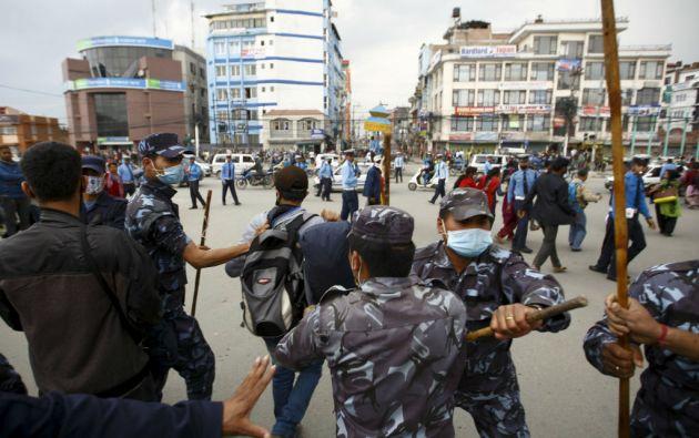 Agentes antidisturbios intentan controlar a un grupo que intentaba bloquear el tráfico ante la desesperación por la falta de ayuda. Foto: REUTERS