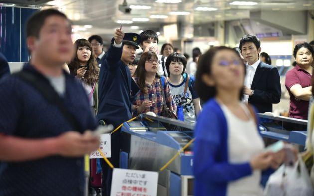 Pasajeros esperan que se reanuden los recorridos de los trenes en una central en Tokio. Foto: AFP