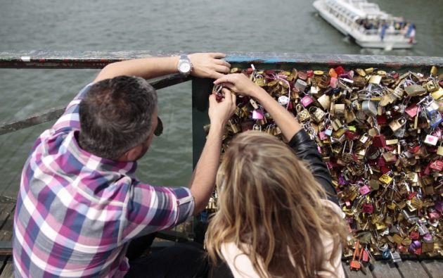 Una pareja coloca un candado en el puente. Foto: AFP.