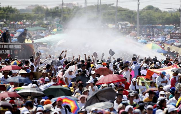 Miembros del Cuerpo de Bomberos rocían con agua a los asistentes a la misa en parque Samanes para aplacar el intenso calor. Foto: REUTERS