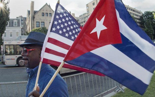 Un hombre ondea las banderas de Cuba y EE.UU. frente a la embajada cubana en Washington. Foto: AFP
