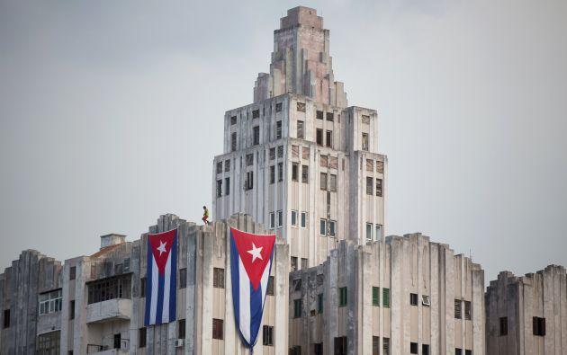 Un hombre cuelga banderas cubanas en un edificio cerca de la embajada de EEUU en La Habana, dos días antes de la visita de Kerry. Foto: REUTERS.
