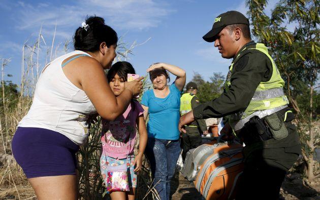 Una mujer besa a su hija antes de enviarla con un policía colombiano, quien la llevaría a Colombia a través del río Táchira. Foto: REUTERS.