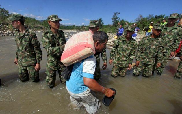 Militares ayudan a un colombiano a dejar Venezuela a través del río Táchira. Foto: AFP.