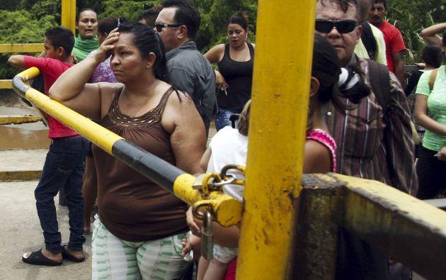 Un grupo de personas espera detrás de una puerta cerrada para cruzar el puente La Unión, desde Boca de Grita, en Táchira (Venezuela) hacia Colombia. Foto: REUTERS.