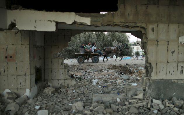 Palestinos a caballo pasan cerca de una casa destruida en un bombardeo en el verano pasado, en el norte de la Franja de Gaza. Foto: REUTERS.
