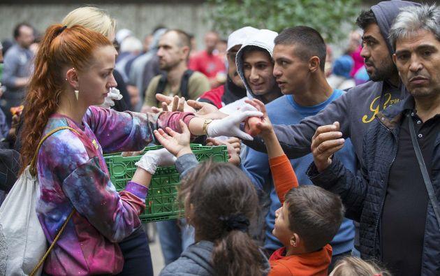 Una voluntaria reparte fruta en Berlín. Foto: REUTERS.