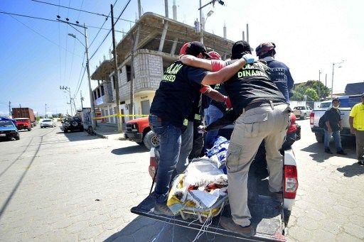 Agentes de la DINASED trasladan los cadáveres en Pedernales. Foto: Agencia AFP