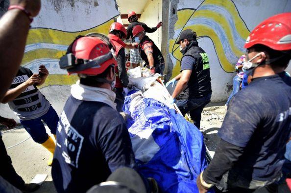 Rescatistas trasladan un cuerpo en Pedernales. Foto: AFP