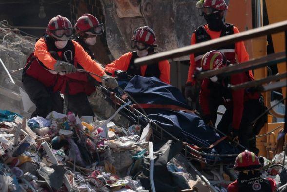 Un grupo de rescatistas levantan un cuerpo de los escombros de una edificación de Manta. (Foto: AFP)