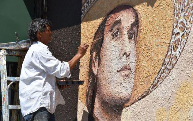 Fotografía del pintor salvadoreño Héctor Ponce que agrega los últimos detalles al mural dedicado al fallecido cantautor mexicano.