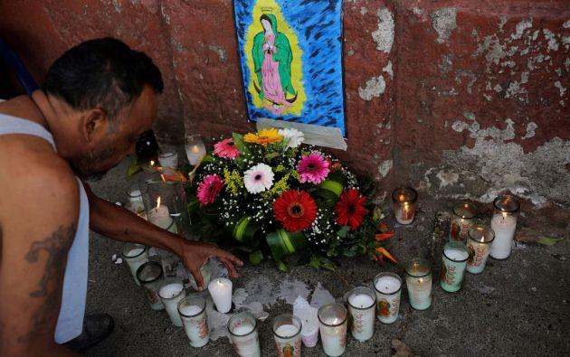 Un familiar de una de las víctimas coloca una vela en su memoria.   Foto: Reuters.