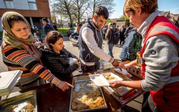 Los miembros de las ONGs dan comida a los inmigrantes kurdos después de que un enorme incendio destruyó el campamento Grande-Synthe. Foto: AFP