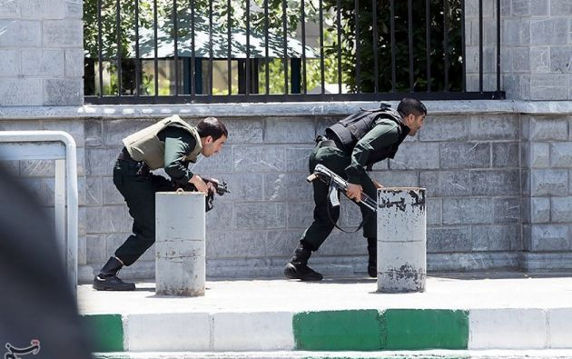 Dos miembros de seguridad se protegen durante el ataque al Parlamento. | Foto: Reuters.