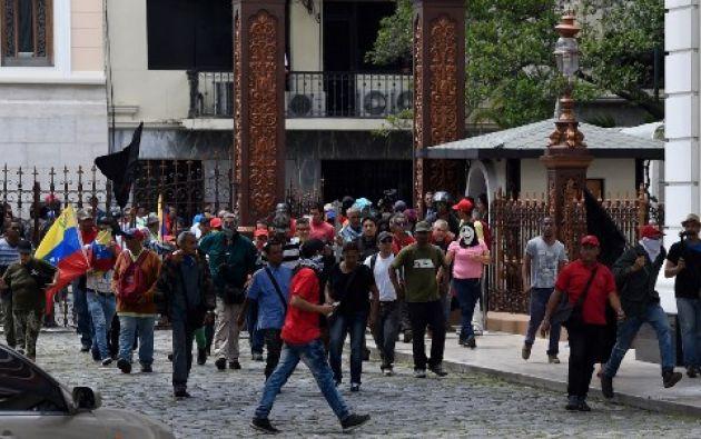 Decenas de personas, algunas encapuchadas, con palos y vestidas de rojo, entraron a los jardines del Palacio Legislativo y detonaron cohetes de fuegos artificiales, desatando el caos.| Foto: AFP
