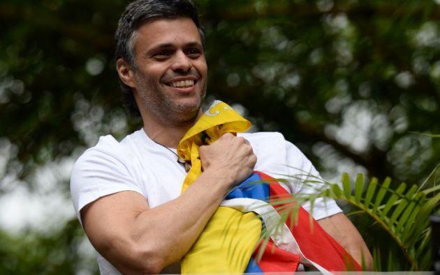 VENEZUELA.- El líder opositor Leopoldo López ondea la bandera de su país tras pasar de cárcel a casa su condena por 13 años. Foto: AFP