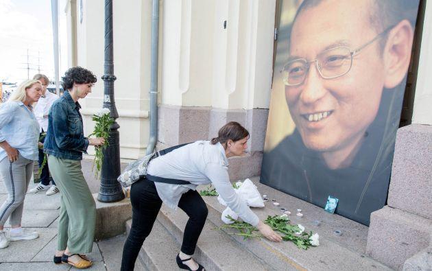 Varias personas dejan su homenaje en el centro del Nobel en Estocolmo tras la muerte del activista chino Liu Xiaobo. Foto: Reuters