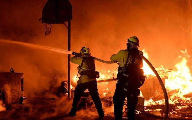 Los bomberos luchan día y noche bajo una espesa nube de humo negro por combatir las llamas en seis frentes. Foto: Reuters