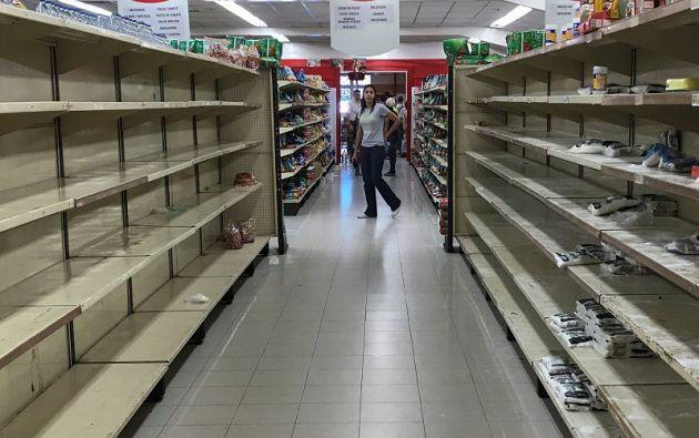 Una mujer pasa por estantes vacíos en un supermercado en Caracas. Foto: Reuters