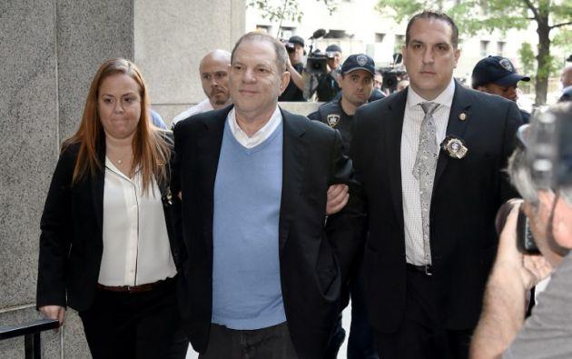 Siete meses después de que comenzaran a llover las denuncias contra él, a Weinstein se le vio hoy por primera vez esposado, pero a pesar de todo sonriente. Foto: AFP