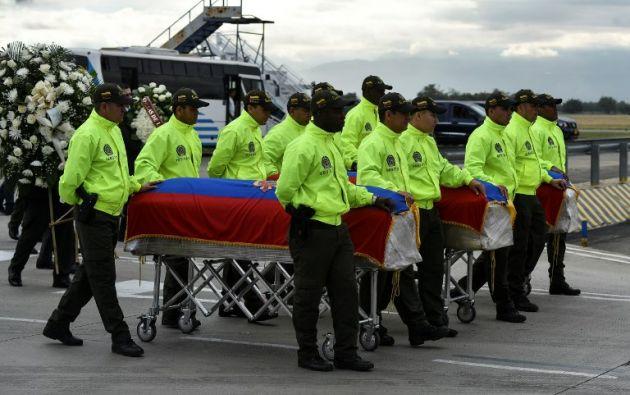 El paso de los féretros hasta las carrozas se vio acompañado por música interpretada por la banda de la Policía. Foto: AFP