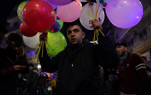 ALEPO, Siria.- Joven sostiene unos globos para conmemorar las fiestas de Año Nuevo. Foto: AFP.