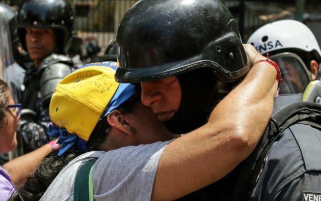 Una partidaria del presidente interino Juan Guaido abraza a un policía durante una manifestación en Caracas el 9 de marzo de 2019. Foto: AFP
