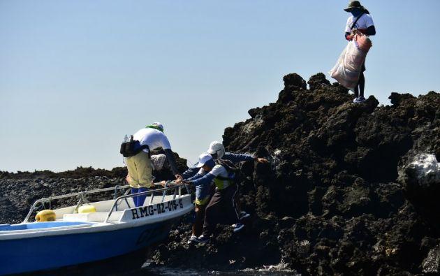 Guardaparques y voluntarios recogen la basura que se acumula en las costas, evitando así que esta basura siga degradándose y que llegue a convertirse en microplástico. AFP
