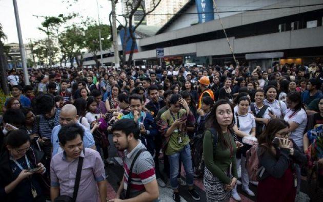 Trabajadores del centro de Manila son evacuados durante el terremoto que se sintió hoy en Filipinas. Foto: AFP.
