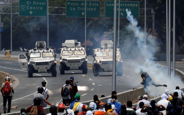 """Manifestantes de la oposición se enfrentan a vehículos militares cerca de la base aérea del Generalísimo Francisco de Miranda """"La Carlota"""" en Caracas, Venezuela. Foto: Reuters."""