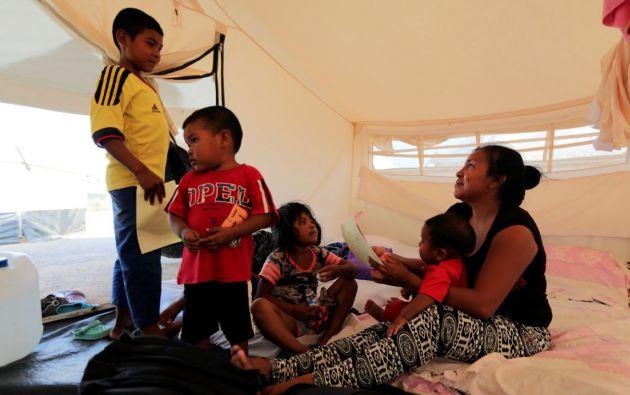 María Moreno, de 28 años, madre migrante venezolana, habla con sus hijos dentro de una tienda de campaña de ACNUR en Maicao, Colombia. Foto: Rueters.