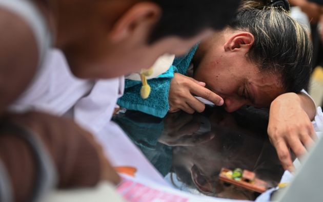 La madre de Erick llora sobre su tumba. El pequeño de 11 años nunca recibió el trasplante que esperaba. Foto: AFP.