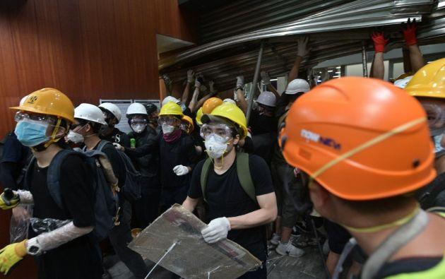 Los asaltantes, ataviados con cascos y máscaras antigas, destrozaron varias de las entradas del complejo. Foto: AFP