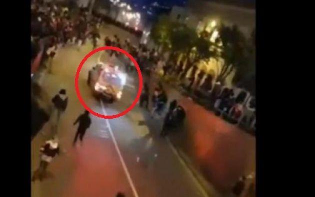 Manifestantes lanzan objetos contra una ambulancia que avanza con las sirenas encendidas.